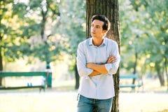 Hübscher erwachsener Mann, der auf einem Baum sich lehnt stockfotos
