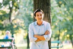 Hübscher erwachsener Mann, der auf einem Baum sich lehnt stockbild