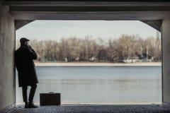 hübscher erwachsener Mann mit dem Koffer, der im Tunnel vor raucht lizenzfreie stockbilder
