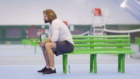 Hübscher erwachsener Mann mit Schläger sitzen auf Bank am Tennisplatz stock footage