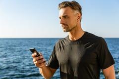 hübscher erwachsener Mann mit Smartphone auf Küste lizenzfreies stockfoto