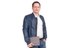 Hübscher europäischer Mann in der blauen Lederjacke mit Tablet-PC in seinen Händen lokalisiert auf weißem Hintergrund Lizenzfreie Stockfotografie
