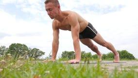 Hübscher flexibler athletischer Mann, der Yoga asanas im Park tut stock footage