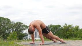 Hübscher flexibler athletischer Mann, der Yoga asanas im Park tut stock video