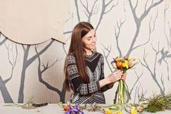 Hübscher Florist, der Blumenstrauß von den Frühlingsblumen macht Lizenzfreie Stockfotografie