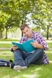 Hübscher fokussierter Student, der auf dem Grasstudieren sitzt Stockfoto