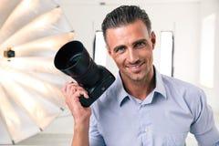 Hübscher Fotograf, der Kamera hält Stockbilder