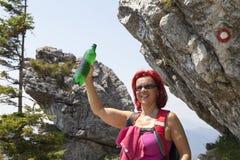 Hübscher Frau Trekker, der unter großem Felsen mit Wegweiser trinkt Stockbilder