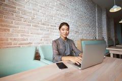 Hübscher Frauenfreiberufler, der Netzbuch für Telearbeit verwendet Lizenzfreie Stockfotos