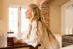 Hübscher Frauentag das Lehnen auf dem Zähler träumend Stockbilder