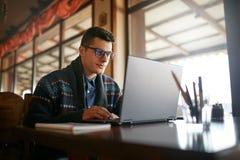 Hübscher Freiberuflergeschäftsmann, der an Laptop im Café arbeitet Bloggermann, der sein Profil in den sozialen Netzwerken mit ak Stockfoto
