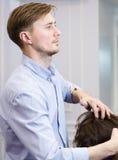 Hübscher Friseur, der einen Haarschnitt macht Stockfotografie