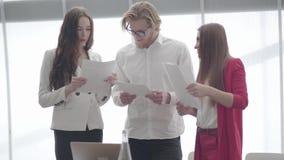 Hübscher Geschäftsmann in den Gläsern Dokumente mit zwei weiblichen Kollegen, die vor großem Fenster in a besprechend stehen stock video