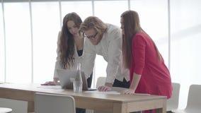 Hübscher Geschäftsmann in den Gläsern verbogen über netbook in einem hellen bequemen Büro, das den weiblichen Kollegen Informatio stock video footage