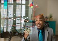 Hübscher Geschäftsmann, der auf ein futuristisches Finanzdiagramm zeigt stockfotografie