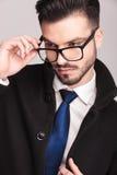 Hübscher Geschäftsmann, der auf seine Gläser sich setzt Lizenzfreies Stockbild