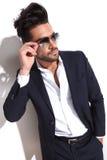 Hübscher Geschäftsmann, der auf seine Sonnenbrille sich setzt Stockfotos