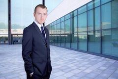 Hübscher Geschäftsmann, der auf Straße gegen Bürogebäude steht Lizenzfreie Stockfotografie
