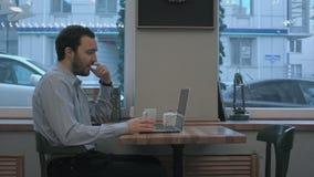Hübscher Geschäftsmann, der durch Videochat auf Laptop im Café spricht stock video