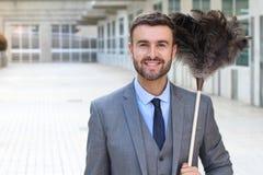 Hübscher Geschäftsmann, der ein Federstaubtuch hält lizenzfreies stockbild