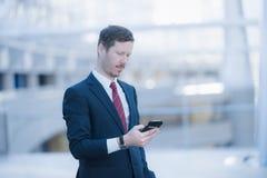 Hübscher Geschäftsmann, der eine Mitteilung an seinem Mobiltelefon empfängt Stockfoto