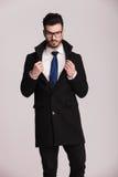 Hübscher Geschäftsmann, der einen langen schwarzen Mantel trägt Stockbild