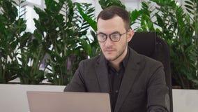 Hübscher Geschäftsmann, der einen Laptop betrachtet Kamera und das Lächeln verwendet stock footage