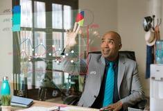 Hübscher Geschäftsmann, der futuristisches Finanzdiagramm verwendet Stockbild