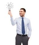 Hübscher Geschäftsmann, der Glühlampe hält Stockbild