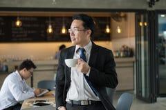 Hübscher Geschäftsmann, der an Hand einen Tasse Kaffee steht und hält Erfolgreiches Konzept des Geschäfts stockfotografie