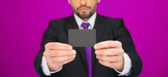 Hübscher Geschäftsmann, der leere Visitenkarte zeigt Stockfotografie