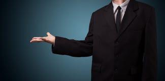 Hübscher Geschäftsmann, der mit Handkopienraum sich darstellt Lizenzfreie Stockfotos