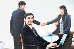 Hübscher Geschäftsmann, der mit Laptop im Büro arbeitet Stockfotografie