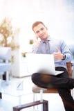 Hübscher Geschäftsmann, der mit Laptop im Büro arbeitet Lizenzfreie Stockfotografie