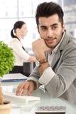 Hübscher Geschäftsmann, der am Schreibtisch sitzt lizenzfreie stockfotos