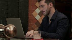 Hübscher Geschäftsmann, der an seinem Laptop beim Etwas trinken in einer noblen Bar arbeitet stock video footage