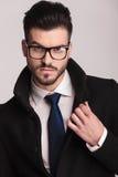 Hübscher Geschäftsmann, der seinen Kragen repariert Stockfotografie