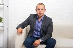 Hübscher Geschäftsmann, der zu Hause auf Couch im Wohnzimmer, Kamera schauend sitzt Lizenzfreie Stockbilder