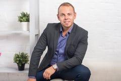Hübscher Geschäftsmann, der zu Hause auf Couch im Wohnzimmer sitzt Lizenzfreie Stockfotos
