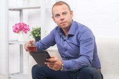 Hübscher Geschäftsmann, der zu Hause auf Couch mit Laptop im Wohnzimmer, Kamera schauend sitzt Stockfoto