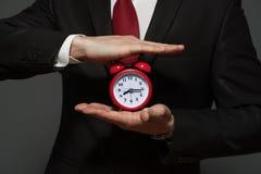 Hübscher Geschäftsmann im Gesellschaftsanzug, der Uhr hält Stockfotografie