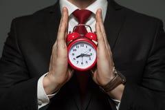 Hübscher Geschäftsmann im Gesellschaftsanzug, der Uhr hält Lizenzfreies Stockfoto