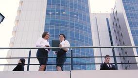 Hübscher Geschäftsmann kommt auf die Terrasse des Bürogebäudes, während zwei attraktive Geschäftsdamen plaudern stock video