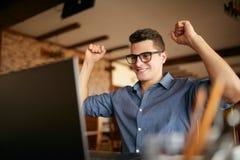 Hübscher Geschäftsmann mit dem Laptop, der seine Arme mit den Fäusten angehoben, Erfolg feiernd hat Glücklicher Freiberuflerhippi lizenzfreie stockbilder