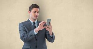 Hübscher Geschäftsmann unter Verwendung des intelligenten Telefons über beige Hintergrund Lizenzfreies Stockfoto