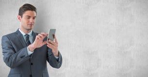 Hübscher Geschäftsmann unter Verwendung des intelligenten Telefons gegen Wand Stockfoto