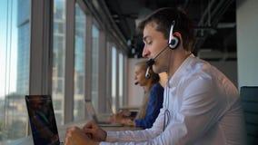Hübscher Geschäftsmannunternehmer im Kopfhörer nennend zu den cuctomers in der Geschäftsaufsuchen in der praxis-Mitte stock video