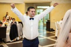 Hübscher glücklicher Bräutigam im weißen Hemd, das Spaß während des ersten danc hat stockfotos