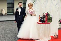 Hübscher glücklicher Bräutigam und schöne blonde Braut in weißem Kleid a Stockbild