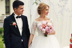 Hübscher glücklicher Bräutigam und schöne blonde Braut in weißem Kleid a Lizenzfreies Stockbild